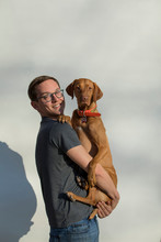 Caucasian Millennial Male Construction Worker In Front Of White Wall Holding Dog