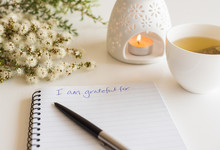 "Close Up Of Handwritten Text ""I Am Grateful For..."" In Foreground With Notebook, Pen,  Cup Of Tea, Flowers And Oil Burner In Soft Focus (deliberate Angle)"