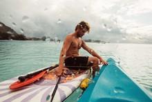 Man Sits With Kayak On Tropica...