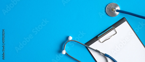 Foto Medical clipboard and stethoscope on blue background