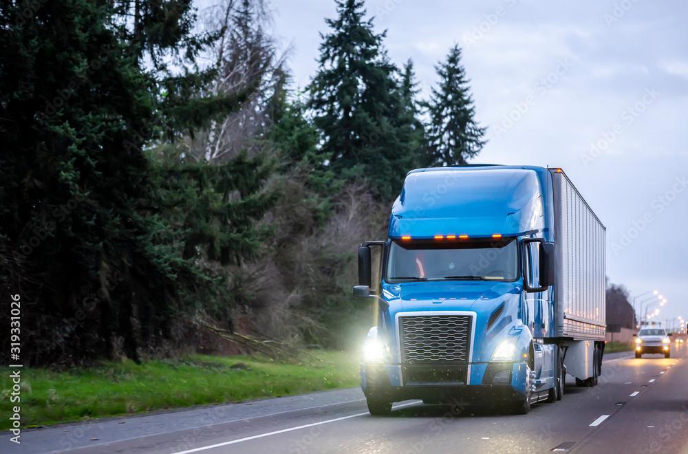 Fototapeta Blue big rig semi truck with dry van semi trailer running on the twilight highway with turned on headlights and drops of beginning rain
