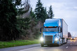 canvas print picture - Blue big rig semi truck with dry van semi trailer running on the twilight highway with turned on headlights and drops of beginning rain