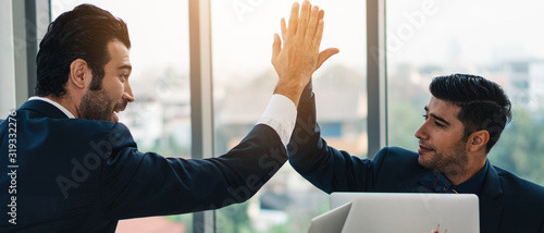 Fotografia business background of two businessmen having high five together showing success