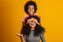 African American Boy Holding His Mother Closed Eyes. Yellow Background. Mothers Day. Brazilian Family.