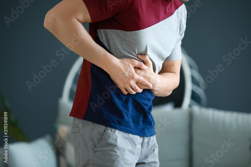 Vászonkép Young man suffering from abdominal pain at home