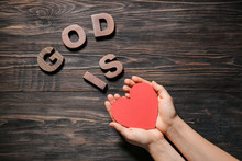 Female Hands And Text GOD IS LOVE On Wooden Background