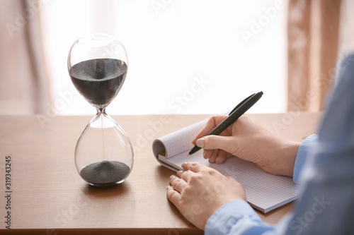 Fototapeta Woman writing something in notebook on table with hourglass in office. Time management concept obraz