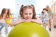 Children in the gym. Preschool kid girl with fitball in physical education lesson.