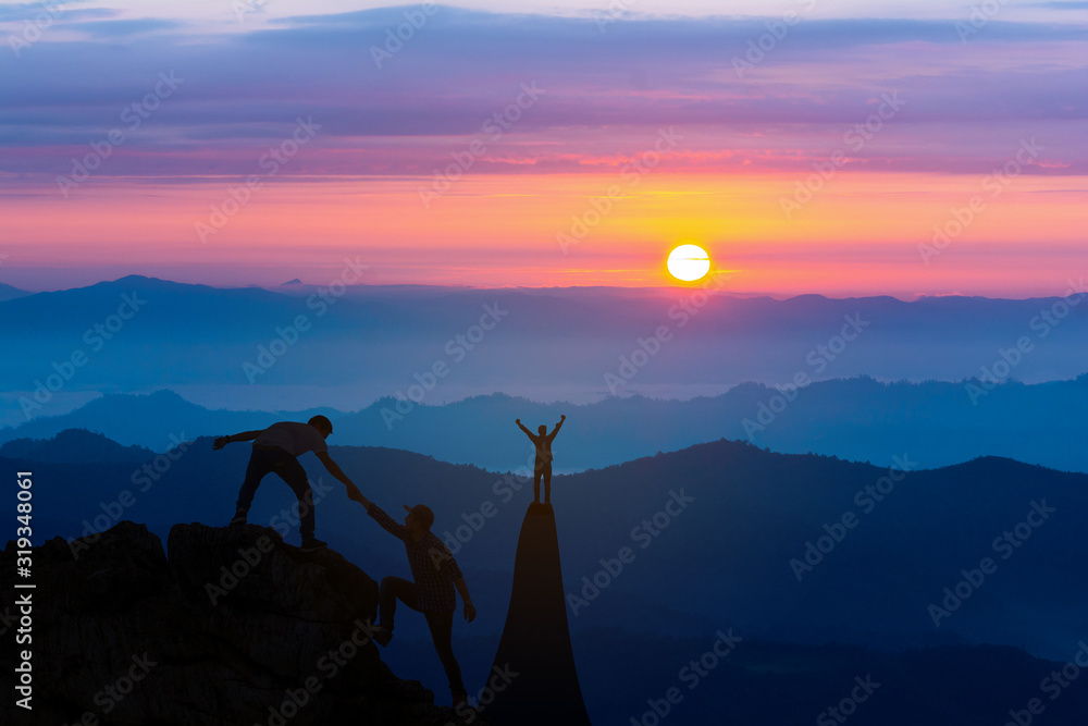 Fototapeta Teamwork friendship hiking help each other trust assistance silhouette in mountains, sunrise. Teamwork of two men hiker helping each other on top of mountain climbing team beautiful sunrise landscape