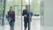 Businessman and businesswoman walking and talking leaving office