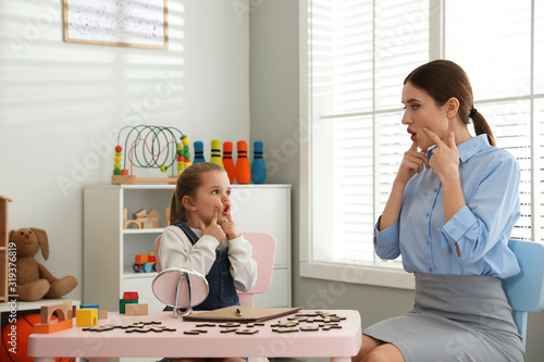 Photo Speech therapist working with little girl in office
