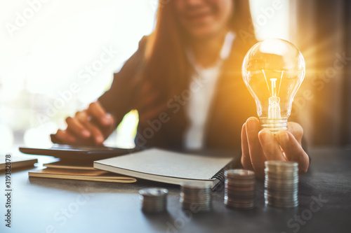 Obraz Businesswoman holding a lightbulb with coins stack on table, saving energy and money concept - fototapety do salonu