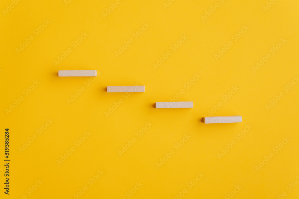 Fototapeta Four blank wooden pegs placed in a stairway like structure