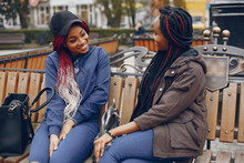 Two Beautiful And Stylish Dark-skinned Girls With Long Hair Sitting On The Bench In A Autumn City