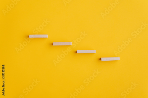 Fototapeta Four blank wooden pegs placed in a stairway like structure obraz