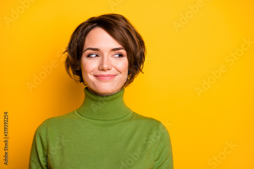 Obraz Closeup photo of funny short hairdo lady charming smiling good mood looking side empty space sly eyes wear casual green warm turtleneck isolated yellow color background - fototapety do salonu