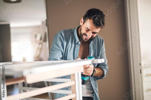 Man assembling slats of baby crib. Tablou Canvas