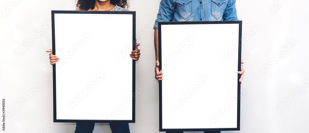 Fototapeta Two friends posing and showing empty white blank board with copy space for text or ad together on white wall background