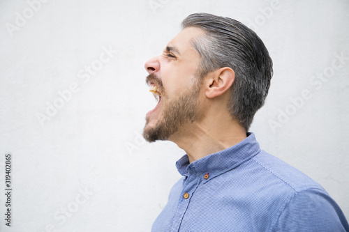 Fotografiet Side view of angry young man screaming