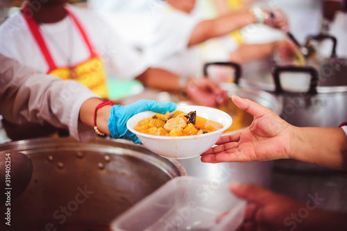 Fotografija The hands of the poor are waiting to receive food from the rich, compassionate,