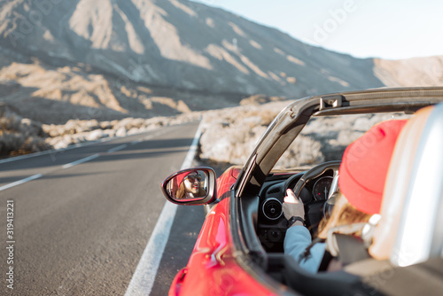 Cuadros en Lienzo Woman driving convertible car on the beautiful desert road, view from the backsi