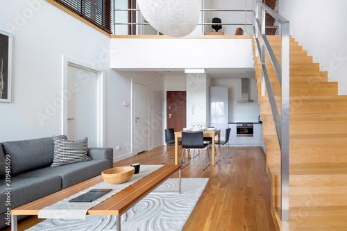 Photo Two-floor open space apartment with wooden stairs and hardwood floor