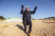 Leinwanddruck Bild - Active senior paraglider on the ground prepairs to fly.