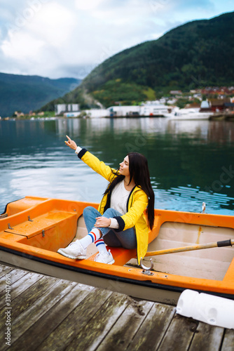 The girl tourist in a yellow jacket is sitting and posing in a boat against the backdrop of the mountains in the Norway Canvas Print