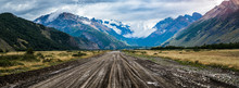 Panorama Of The Dirty Road And Mountains Covered In Snow