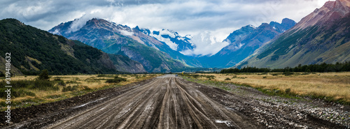 Fotografia Panorama of the dirty road and mountains covered in snow