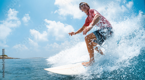 Fotomural Young caucasian man surfs the ocean wave and makes a lot of splashes into the camera