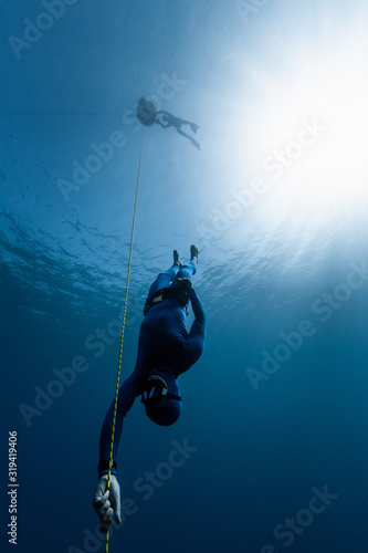 Photo Freediver descends along the rope into the depth while another freediver relaxes