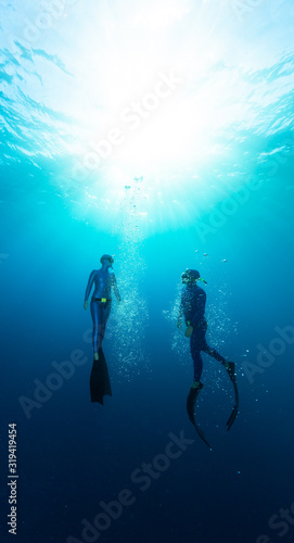 Two freedivers ascend from the depth surrounded by bubbles Wallpaper Mural