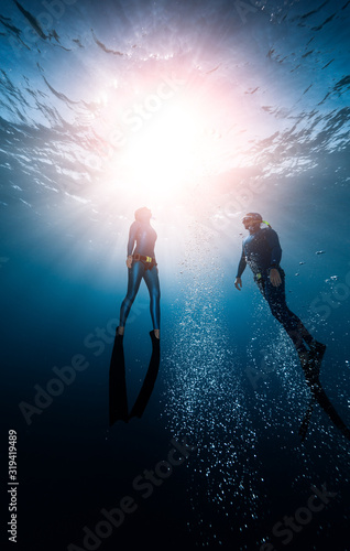 Two freedivers ascend from the depth surrounded by bubbles Canvas Print