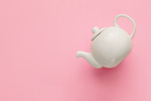White Porcelain Teapot On A Pink Background, Minimal Art, Close-up, Flat Lay