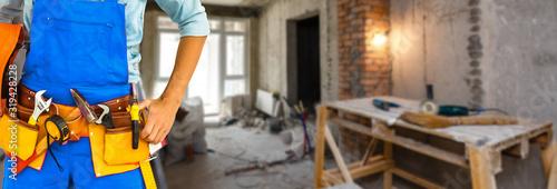 Obraz Builder handyman with construction tools. House renovation background. - fototapety do salonu