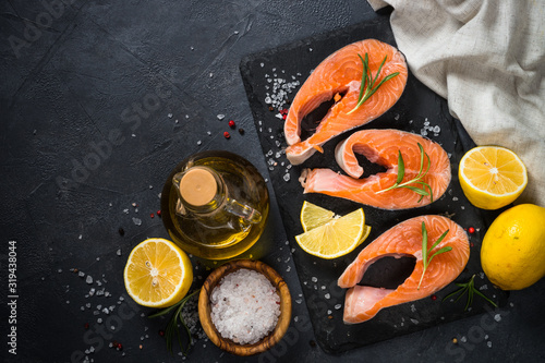 Obraz na plátně Raw salmon steak on black top view.