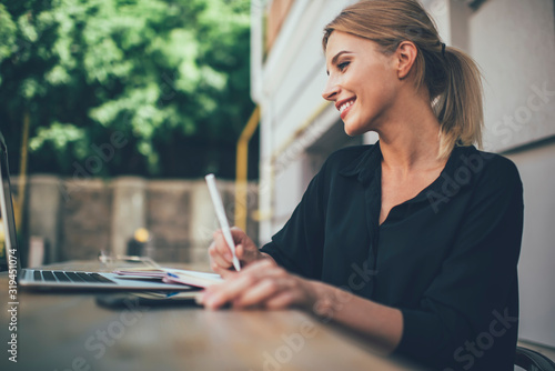 Obraz Satisfied female remote worker with laptop at outdoors cafe veranda - fototapety do salonu