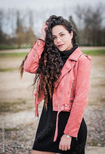 Fotomural belle jeune femme brune au cheveux longs avec lunette et veste en cuir rose
