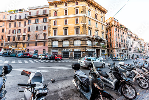Rome, Italy - September 5, 2018: Italian street outside in historic city in morning wide angle road with nobody and parked motorcycle in Monti neighborhood