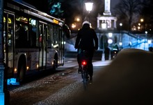 Cyclist Riding Alongside The Bus In The Illuminated City At Night