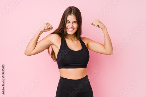 Young caucasian fitness woman doing sport isolated showing strength gesture with arms, symbol of feminine power
