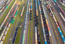 Aerial Perspective View Of Railroad Tracks, Cargo Sorting Station. Many Different Railway Cars With Cargo And Raw Materials.