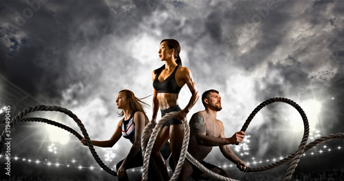 Fototapeta Sporty woman and man working out with battle ropes. Sports banner. obraz
