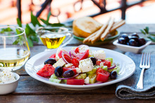 Greek Salad. Fresh Vegetables, Feta Cheese And Black Olives With White Wine. Outdoor Background.