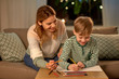 family, leisure and people concept - mother and little son with colored pencils and paper draw at home