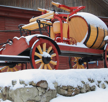 On A Stone Pedestal Stands An Old Fire Cart With A Water Barrel And A Pump. Everything Is Covered With Fresh Snow.