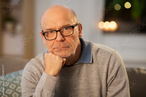 obraz PCV old age and people concept - sad senior man in glasses thinking at home in evening