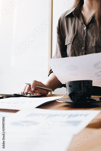 Photo Close up Business woman using calculator and laptop for do math finance on woode