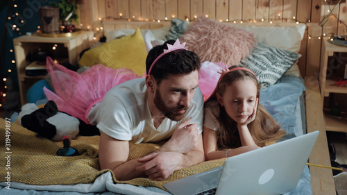 Fotografia Side view of happy father and daughter dressed like fairies watching cartoons on laptop